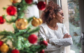 Woman standing by decorated tree staring out window
