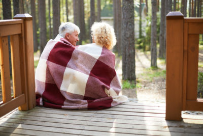 Senior couple sitting on porch with blanket