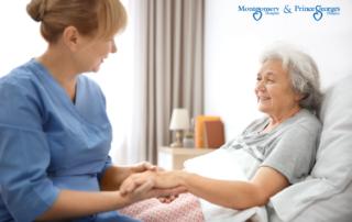 Care provider massaging elderly woman's hand